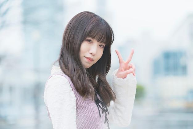 Jonge aziatische vrouw doet een vredesteken met een glimlach buitenshuis