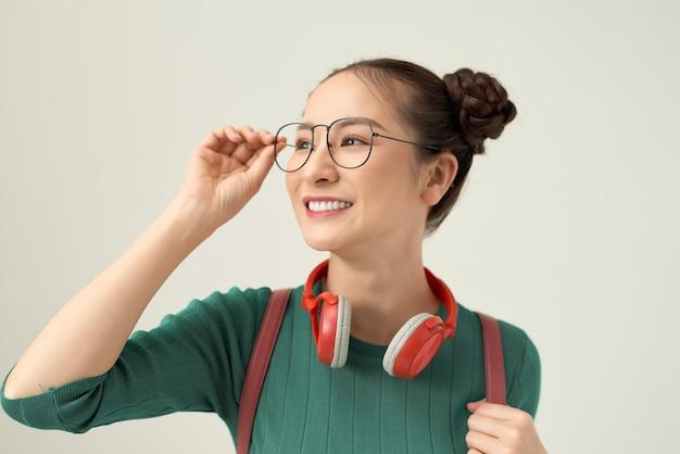 Jonge aziatische vrouw draagt een bril, mooie student met tas.