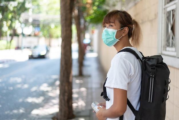Jonge aziatische vrouw draagt een chirurgisch gezichtsmasker voor bescherming in de stad, covid-19-concept
