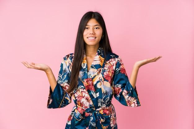 Jonge aziatische vrouw draagt een kimono pyjama maakt schaal met armen, voelt zich gelukkig en zelfverzekerd.