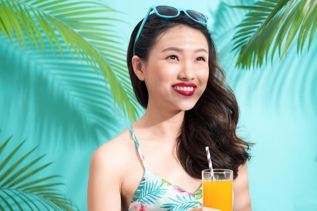 Jonge aziatische vrouw drinkt sap uit glas over kleurrijke blauwe achtergrond