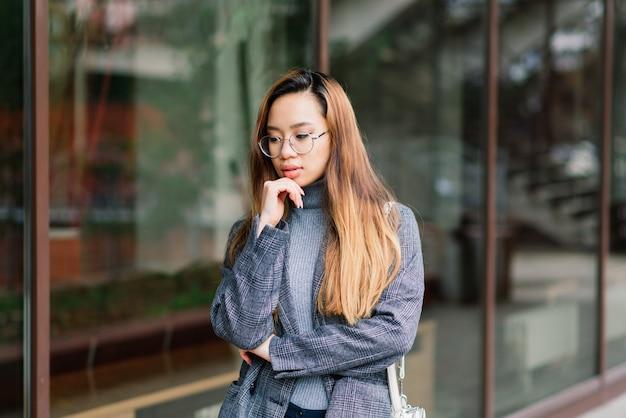 Jonge aziatische vrouw, droevig gezichtsportret in stad bij de avond