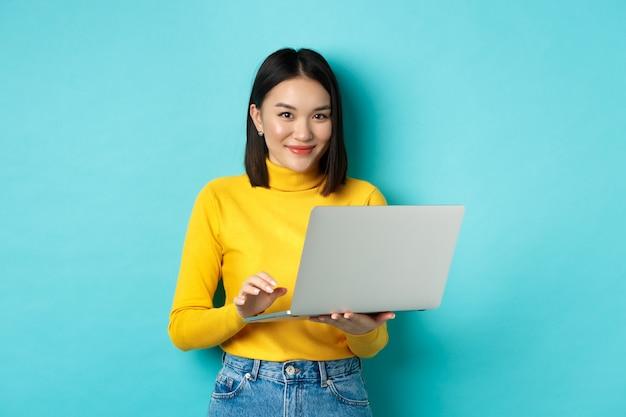 Jonge aziatische vrouw freelancer die op laptop werkt en glimlacht, staande met computer over blauwe achtergrond.