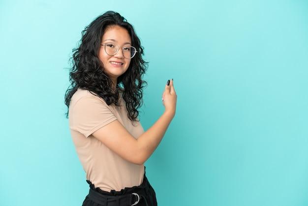 Jonge aziatische vrouw geïsoleerd op een blauwe achtergrond die terug wijst