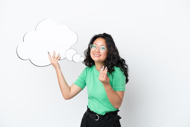 Jonge aziatische vrouw geïsoleerd op een witte achtergrond die een denkende tekstballon houdt en een komend gebaar doet
