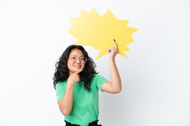 Jonge aziatische vrouw geïsoleerd op een witte achtergrond die een lege tekstballon houdt en erop wijst