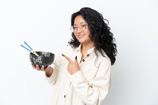Jonge aziatische vrouw geïsoleerd op een witte achtergrond en wijzend terwijl ze een kom noedels met stokjes vasthoudt