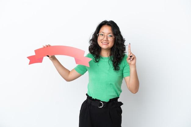 Jonge aziatische vrouw geïsoleerd op een witte achtergrond met een leeg bordje en omhoog