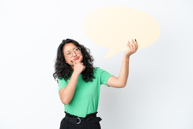 Jonge aziatische vrouw geïsoleerd op een witte achtergrond met een lege tekstballon en denken