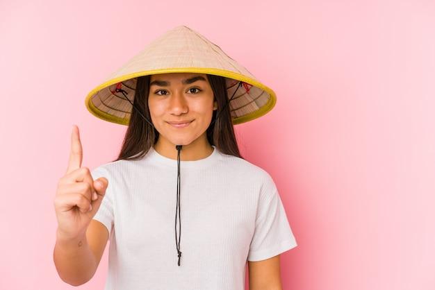 Jonge aziatische vrouw, gekleed in een vietnamese hoed geïsoleerd jonge aziatische vrouw, gekleed in een vietnamese hatshowing nummer één met de vinger.
