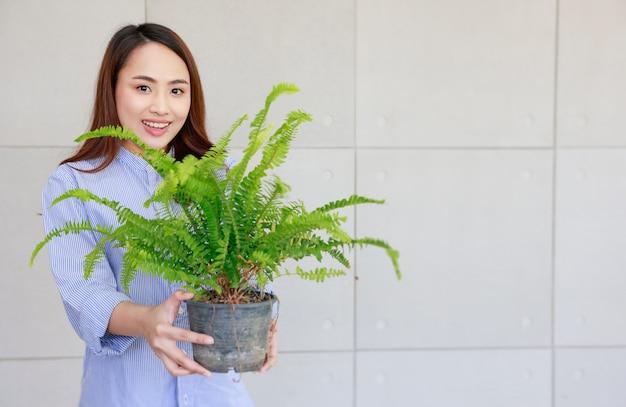 Jonge aziatische vrouw gelukkig lachend en met groene varen in plastic pot te koop tonen.