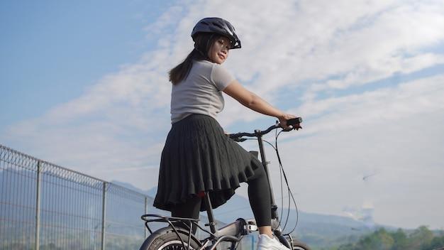 Jonge aziatische vrouw geniet van fietsen wanneer ze in de zomerochtend wordt gestopt
