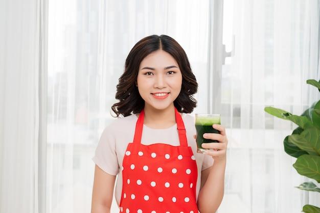 Jonge aziatische vrouw geniet van gezonde vegetarische smoothie voor gewichtsverlies en detox
