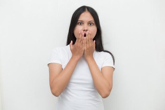 Jonge aziatische vrouw geschokt die mond behandelt met handen