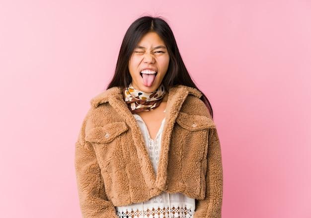 Jonge aziatische vrouw grappige en vriendelijke tong uitsteekt.