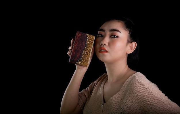 Jonge aziatische vrouw hand met gouden epoxyhars met burl esdoorn houten stok op zwarte achtergrond