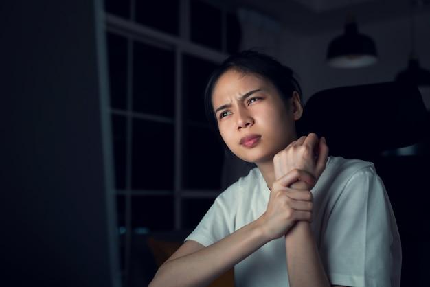 Jonge aziatische vrouw heeft polspijn omdat de computer wordt gebruikt