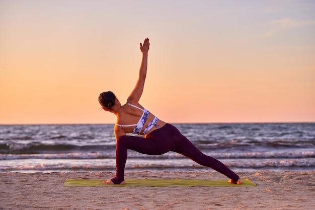 Jonge aziatische vrouw het beoefenen van yoga, het doen van oefeningen, trainen door de zee, het dragen van sportkleding, broeken en top