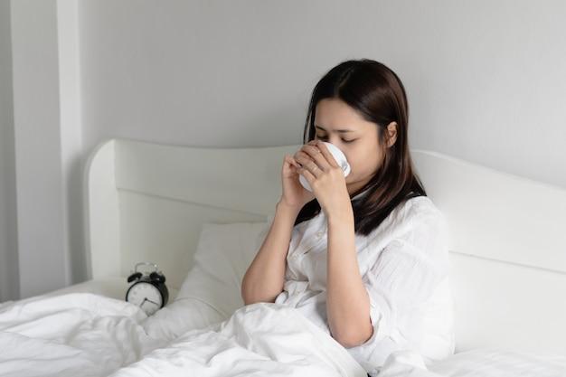 Jonge aziatische vrouw het drinken ochtendkoffie in bed.