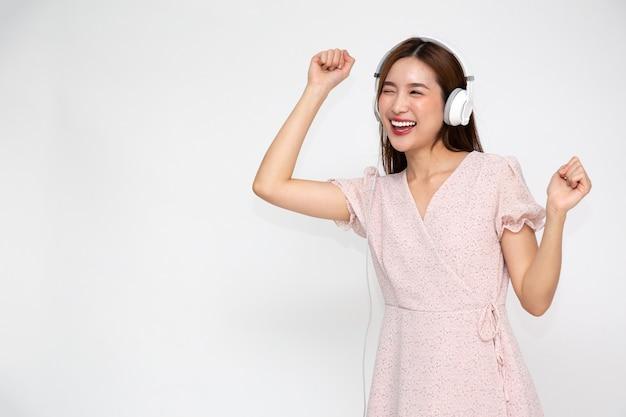 Jonge aziatische vrouw het luisteren muziek met geïsoleerde hoofdtelefoon