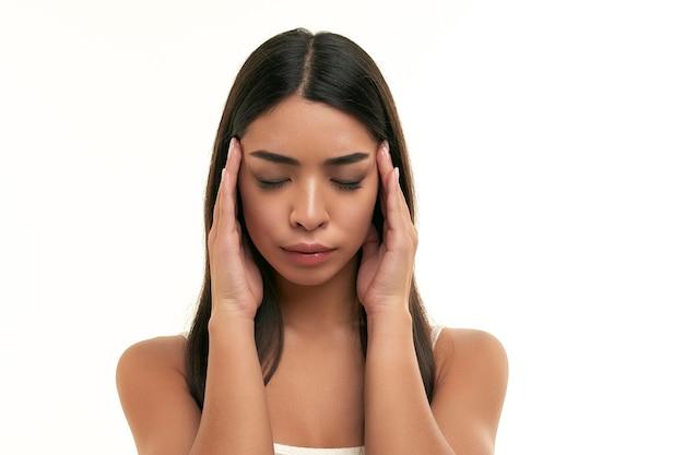 Jonge aziatische vrouw houdt handen op tempels, in stress, depressie, lijdt aan hoofdpijn op wit wordt geïsoleerd