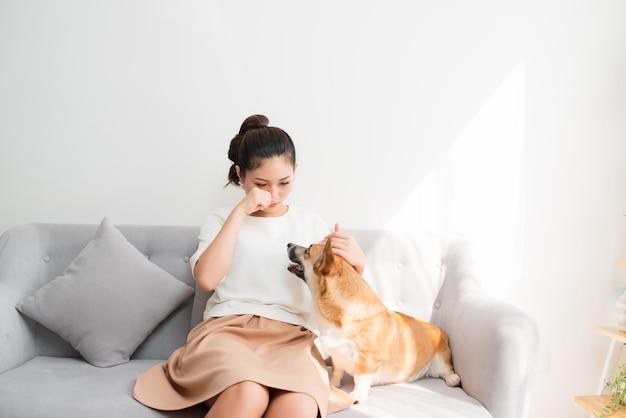 Jonge aziatische vrouw huilt op de bank met haar corgi-hond