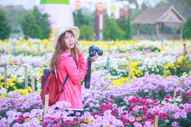 Jonge aziatische vrouw in de chrysantentuin.