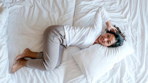 Jonge aziatische vrouw in duidelijke t-shirts op het luxe witte bed