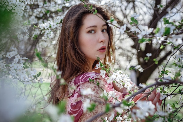 Jonge aziatische vrouw in een bloeiende tuin. romantisch beeld van stijlvolle casual vrouw, trendy zijden blouse. positieve stemming. vrolijke bloesem volle bloei in japan.