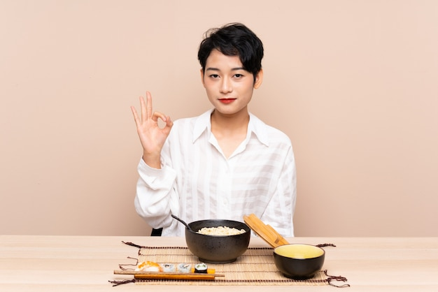 Jonge aziatische vrouw in een lijst met kom van noedels en sushi die een ok teken met vingers tonen