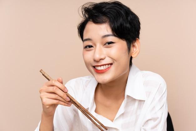 Jonge aziatische vrouw in een tafel met kom noedels en sushi