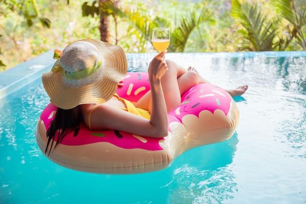 Jonge aziatische vrouw in geel pak zwemmen in een zwembad