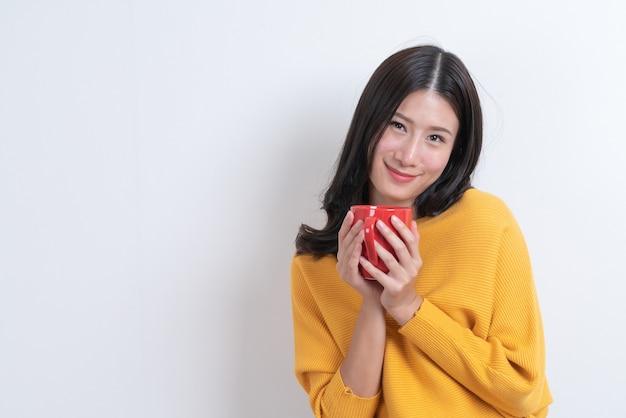 Jonge aziatische vrouw in gele trui met een kopje koffie