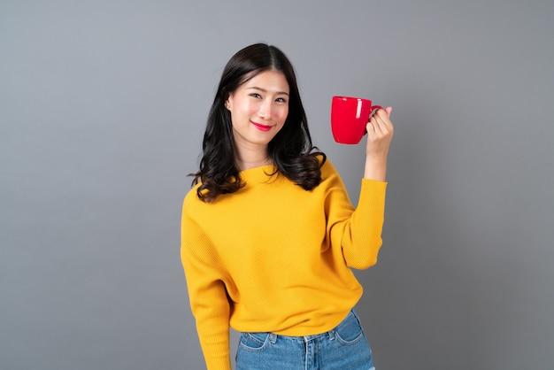 Jonge aziatische vrouw in gele trui met een rode kop koffie, ruikt lekker en geniet van de koffie op grijs