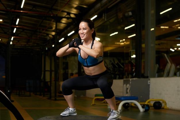 Jonge aziatische vrouw in goede fysieke vorm doet squats in een sportschool