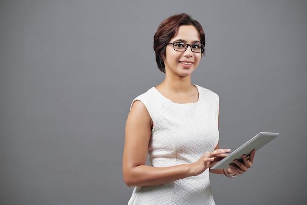 Jonge aziatische vrouw in het slimme kleding stellen in studio met tablet