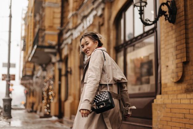 Jonge aziatische vrouw in hoge geesten wandelingen door stad in stijlvolle trenchcoat met kleine zwarte tas