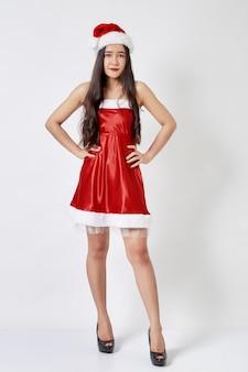 Jonge aziatische vrouw in kerstmanhoed op wit