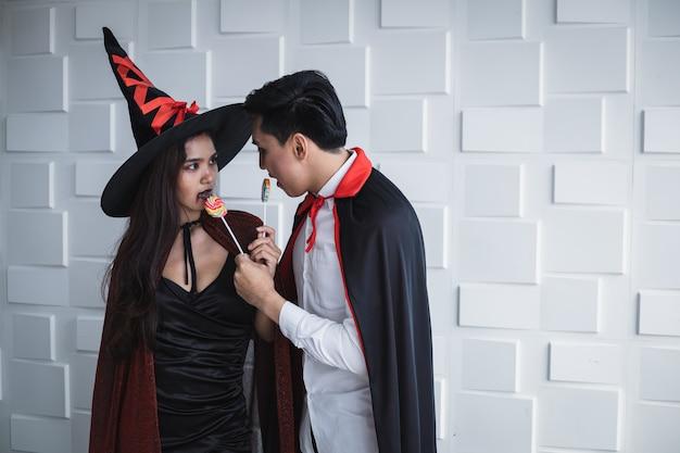 Jonge aziatische vrouw in kostuumheks en aziatische man in kostuumdracula en houd lolly op witte muur van halloween-concept. portret tiener paar verkleed als heksen, dracula voor het vieren van halloween.