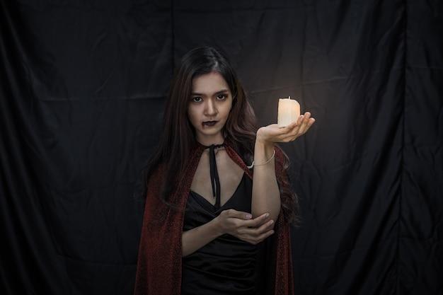 Jonge aziatische vrouw in kostuumheks en houd kaars op zwarte doekachtergrond van halloween-concept. portret van tiener vrouw verkleed als heks voor het vieren van halloween festival.
