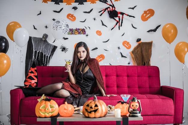 Jonge aziatische vrouw in kostuumheks zit op een rode bank en houdt een wijnglas vast om het halloween-festival in de kamer thuis te vieren. thaise meisjes die halloween thuis vieren.