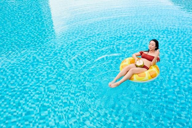 Jonge aziatische vrouw in rode badmode zittend op opblaasbare ring en kokoswater drinken in het zwemmen ...