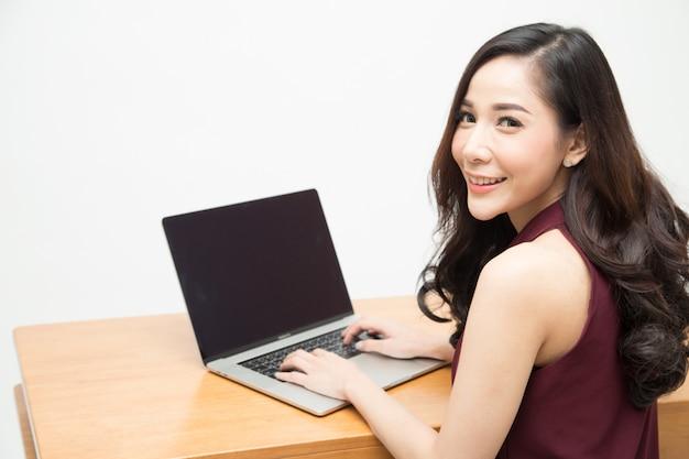 Jonge aziatische vrouw in rode het werkkleren die en met laptop aan de houten lijst glimlachen werken, vrouwen die bij bureau zitten en bij computernotitieboekje werken, zeker onderneemsterconcept