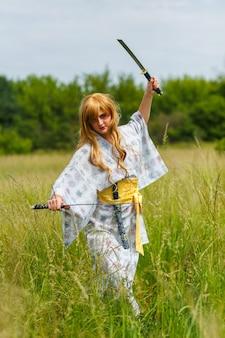Jonge aziatische vrouw in traditionele kimono traint vechttechnieken met katana-zwaard buitenshuis, samoerai-krijgermeisje