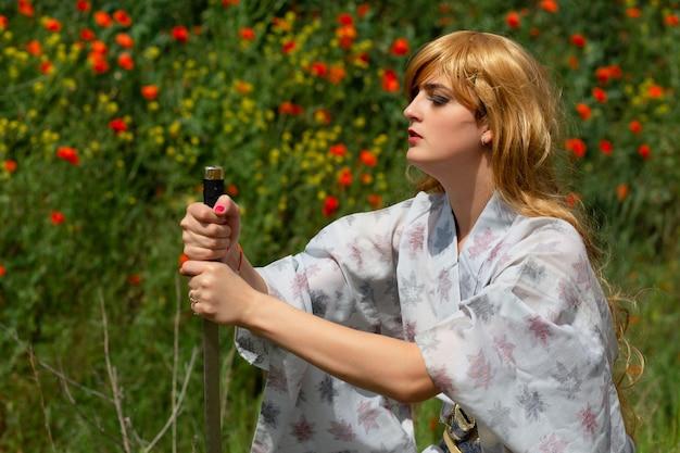 Jonge aziatische vrouw in traditionele kimono traint vechttechnieken met katana-zwaard op de heuvels met rode papavers, samoerai-krijgermeisje