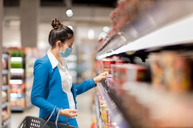 Jonge aziatische vrouw in uniform kantoor met beschermend masker en boodschappen in de supermarkt kopen. concept ter preventie van covid-19 virus.