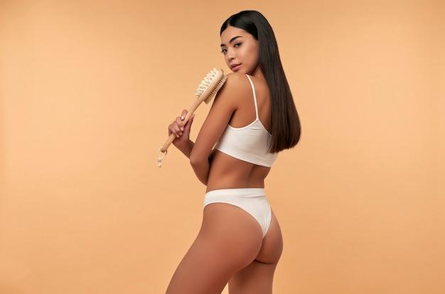 Jonge aziatische vrouw in witte lingerie maakt anti-cellulitis massage met een droge borstel op beige