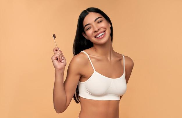 Jonge aziatische vrouw in witte lingerie met een tandenborstel en witte tanden op beige. tandhygiëne concept