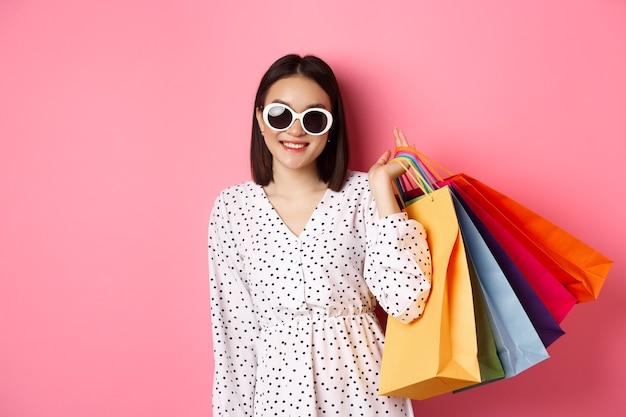 Jonge aziatische vrouw in zonnebril gaan winkelen, tassen uit winkelcentra en winkels te houden en glimlachen, staande over roze