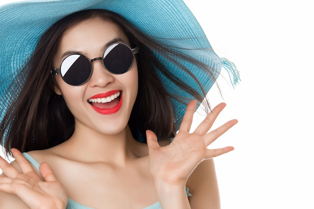 Jonge aziatische vrouw in zonnebril met uitdrukking van verrassing die op wit wordt geïsoleerd.